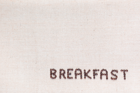 Breakfast word written with coffee beans on creamy linea canvas, shot from above,aligned in the bottom right. Foto de archivo - 122428772