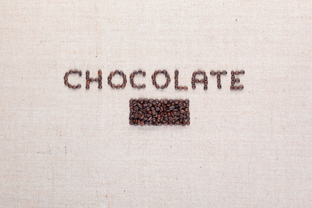 Chocolate word written with coffee beans on creamy linea canvas, shot from above, aligned in center.