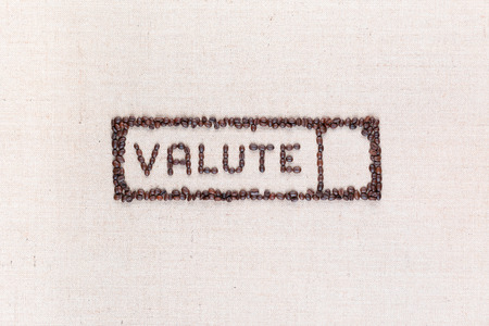 The word valute inside a rectangle written with coffee beans on creamy linea canvas, shot from above,aligned in the center.