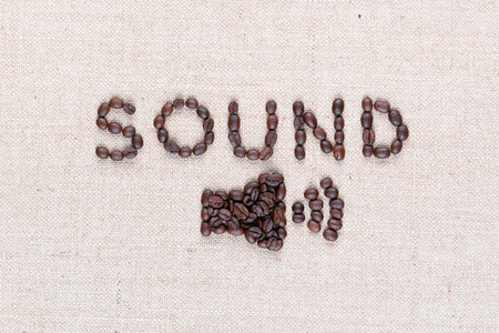 Word Sound and below it a small megaphone all made from coffee beans shot from above,aligned in the center,close up. Imagens