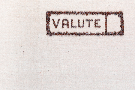 The word valute inside a rectangle written with coffee beans on creamy linea canvas, shot from above,aligned at the top right. 免版税图像