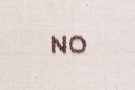 The word No written with coffee beans on creamy linea canvas, shot from above, aligned in the center,close up.