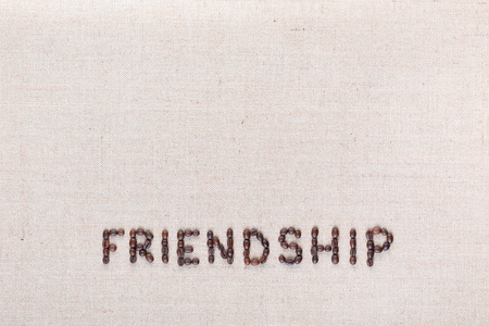 Friendship word written with coffee beans on creamy linea canvas, shot from above, aligned at the bottom.
