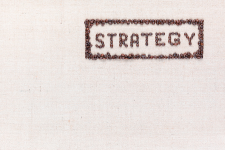 The word Strategy inside a rectangle written with coffee beans on creamy linea canvas, shot from above, aligned to the top right. Foto de archivo - 122428943