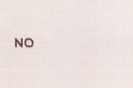 The word No written with coffee beans on creamy linea canvas, shot from above, aligned to the left. Foto de archivo