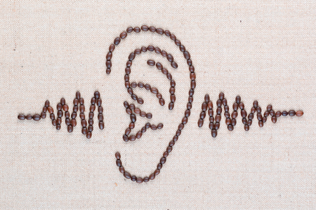 Human ear, through which is passing a sound wave,everything is made from coffee beans and the image is aligned in the center, close up.