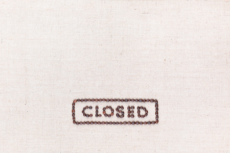 The word Closed inside a rectangle written with coffee beans on creamy linea canvas, shot from above, aligned at the bottom. Stock Photo