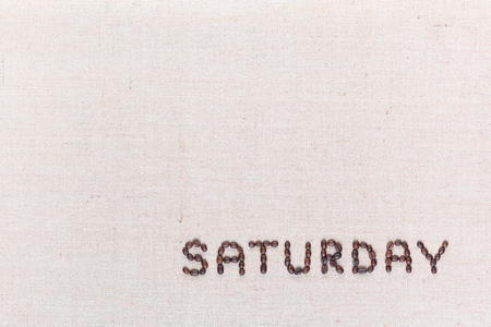 The word Saturday written with coffee beans on creamy linea canvas, shot from above , aligned at the bottom right. 写真素材