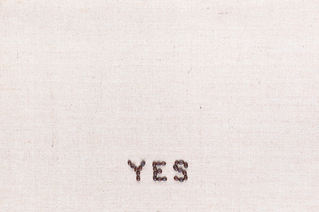 The word Yes written with coffee beans on creamy linea canvas, shot from above, aligned at the bottom.