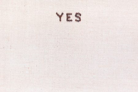 The word Yes written with coffee beans on creamy linea canvas, shot from above, aligned at the top.