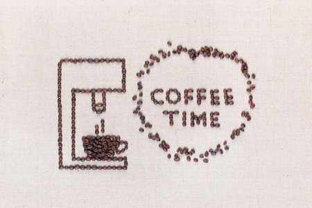 A coffee machine preparing a hot coffee next to the words Coffee Time which are inside a circle all made with coffee beans shot from above, aligned in the center.