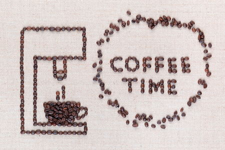 A coffee machine preparing a hot coffee next to the words Coffee Time which are inside a circle all made with coffee beans shot from above, aligned in the center, closeup.