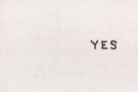 The word Yes written with coffee beans on creamy linea canvas, shot from above, aligned to the right. Stock Photo