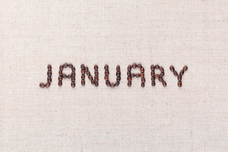 The word January written with coffee beans on creamy linea canvas, shot from above, aligned in the center, closeup. Foto de archivo - 123223094