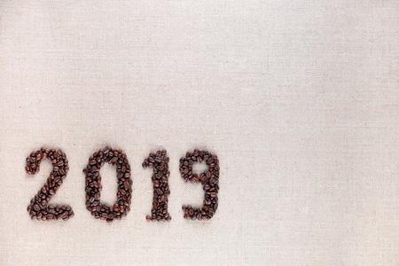 Bunch of fresh roasted coffee beans forming 2019 inscription on creamy linen canvas, aligned bottom left 版權商用圖片