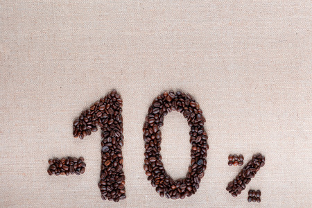 Roasted coffee beans shaping 10% off writing on creamy linen background, aligned at bottom center