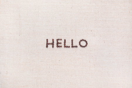 The word Hello written with coffee beans on creamy linea canvas, shot from above, aligned in the center. Foto de archivo - 123218630
