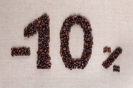 Roasted coffee beans shaping 10% off writing on creamy linen background, aligned in center, shot close up