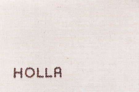 The word Holla written with coffee beans on creamy linea canvas, shot from above, aligned at the bottom left. Foto de archivo - 123218322