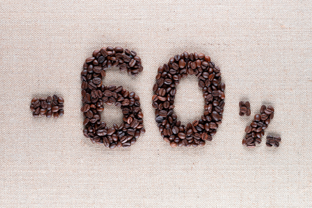 Roasted coffee beans shaping 60% off writing on creamy linen background, aligned in center, shot close up