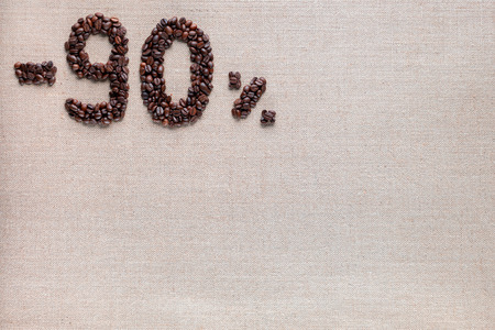 Roasted coffee beans shaping 90% off writing on creamy linen background, aligned top left