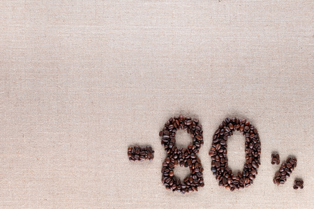 Roasted coffee beans shaping 80% off writing on creamy linen background, aligned bottom right