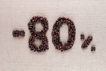 Roasted coffee beans shaping 80% off writing on creamy linen background, aligned in center, shot close up