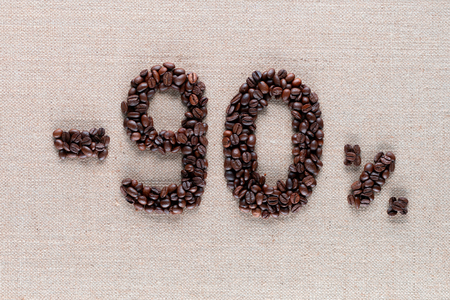 Roasted coffee beans shaping 90% off writing on creamy linen background, aligned in center, shot close up Фото со стока