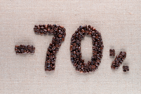 Roasted coffee beans shaping 70% off writing on creamy linen background, aligned in center, shot close up Фото со стока