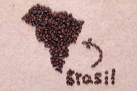 Bunch of fresh roasted coffee beans forming Brazil country on plywood surface, shot close up