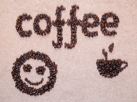 Steamy cup and cute smiley made of roasted beans placed on plywood surface near coffee word