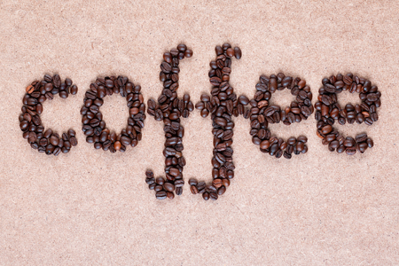Coffee word made of roasted beans placed on plywood texture, shot close up