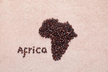 Montón de granos de café tostados frescos que forman el continente africano sobre la superficie de madera contrachapada, alineados en el centro Foto de archivo