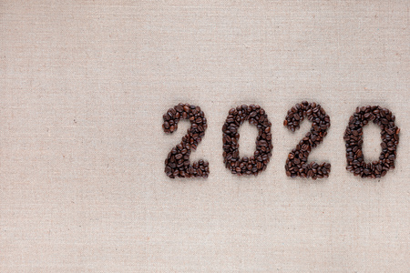 Bunch of fresh roasted coffee beans forming 2020 inscription on creamy linen canvas, aligned middle right 版權商用圖片
