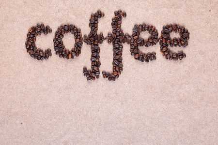Coffee word made of roasted beans placed on plywood texture aligned to the top