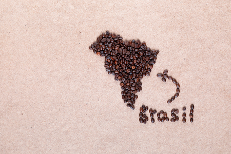 Bunch of fresh roasted coffee beans forming Brazil country on plywood surface, aligned in center
