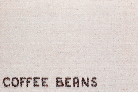 Many roasted seeds forming coffee beans writing against gray canvas background, aligned bottom left 版權商用圖片