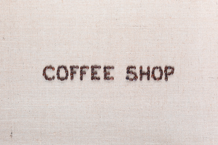 Bunch of roasted beans forming coffee shop inscription on gray canvas, aligned in center