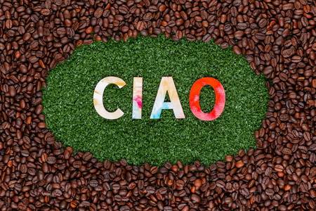 Close up of Ciao word made from colorful letters on artificial grass surrounded by roasted coffee beans