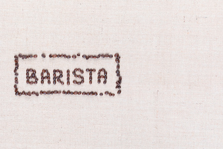 The word Barista inside a rectangle all made with coffee beans on creamy linea canvas, shot from above, aligned to the left. 写真素材