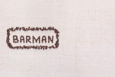 The word Barman written with coffee beans on creamy linea canvas, shot from above, aligned to the left. 写真素材