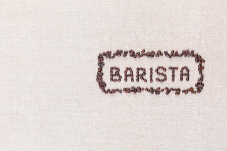 The word Barista inside a rectangle all made with coffee beans on creamy linea canvas, shot from above, aligned to the right.