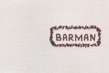 The word Barman written with coffee beans on creamy linea canvas, shot from above, aligned to the right.