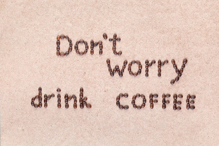 The words Don't worry drink coffee written with coffee beans on creamy linea canvas, shot from above. 免版税图像