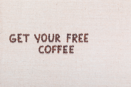 The message Get your free coffee written with coffee beans on creamy linea canvas, shot from above, aligned to the left.