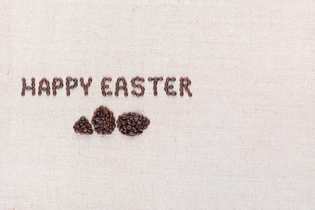 The words Happy easter above some small eggs all made with coffee beans on creamy linea canvas, shot from above, aligned to the left.