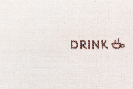 The word Drink near a hot cup of coffee all made with coffee beans on creamy linea canvas, shot from above, aligned to the right.