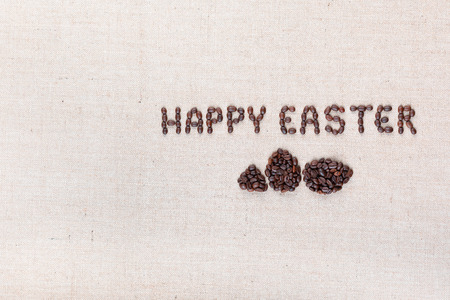 The words Happy easter above some small eggs all made with coffee beans on creamy linea canvas, shot from above, aligned to the right.