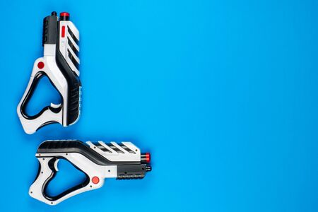 Two black and white toy pistols on blue background shot from above.