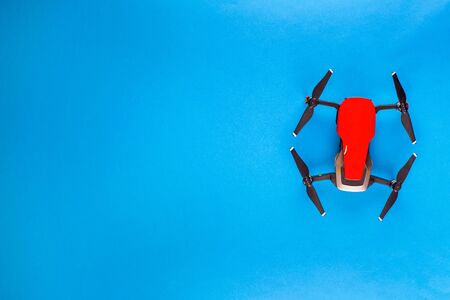 A red drone on blue background, shot from above, aligned to the right.